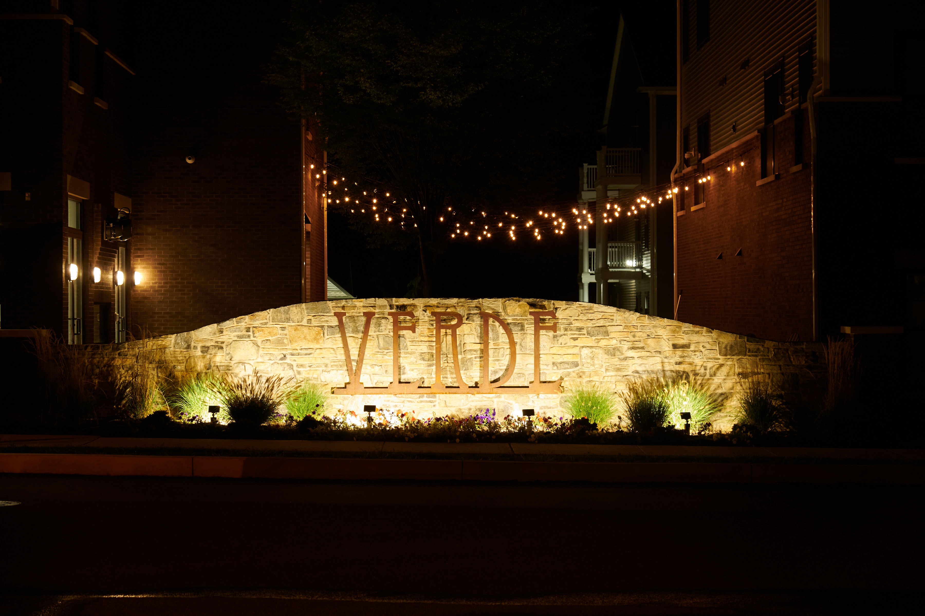 Exterior of Verde Apartments showing the logo with a stone background