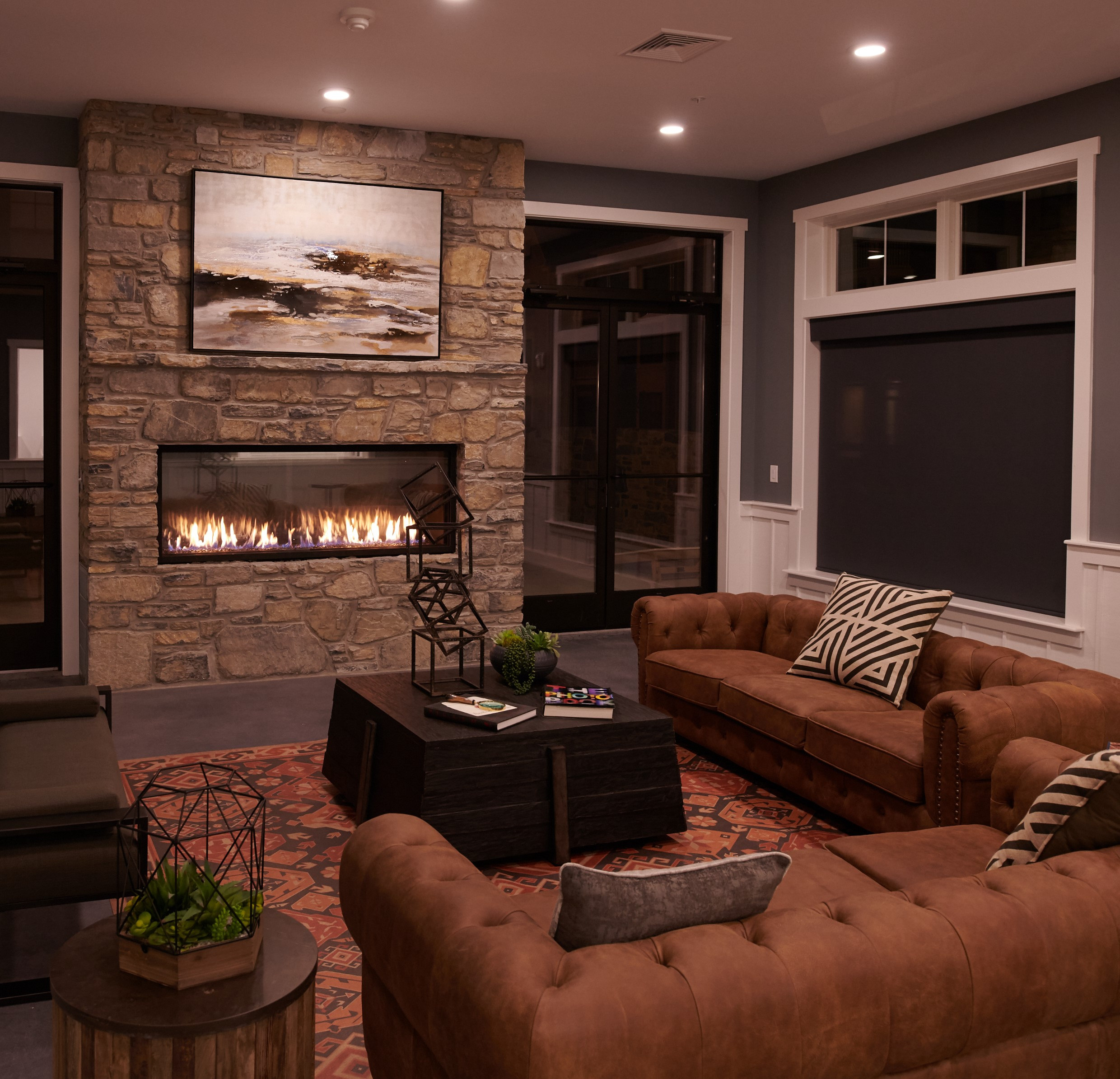Clubhouse at Verde with fireplace surround by stone, two brown couches, and a dark brown coffee table.