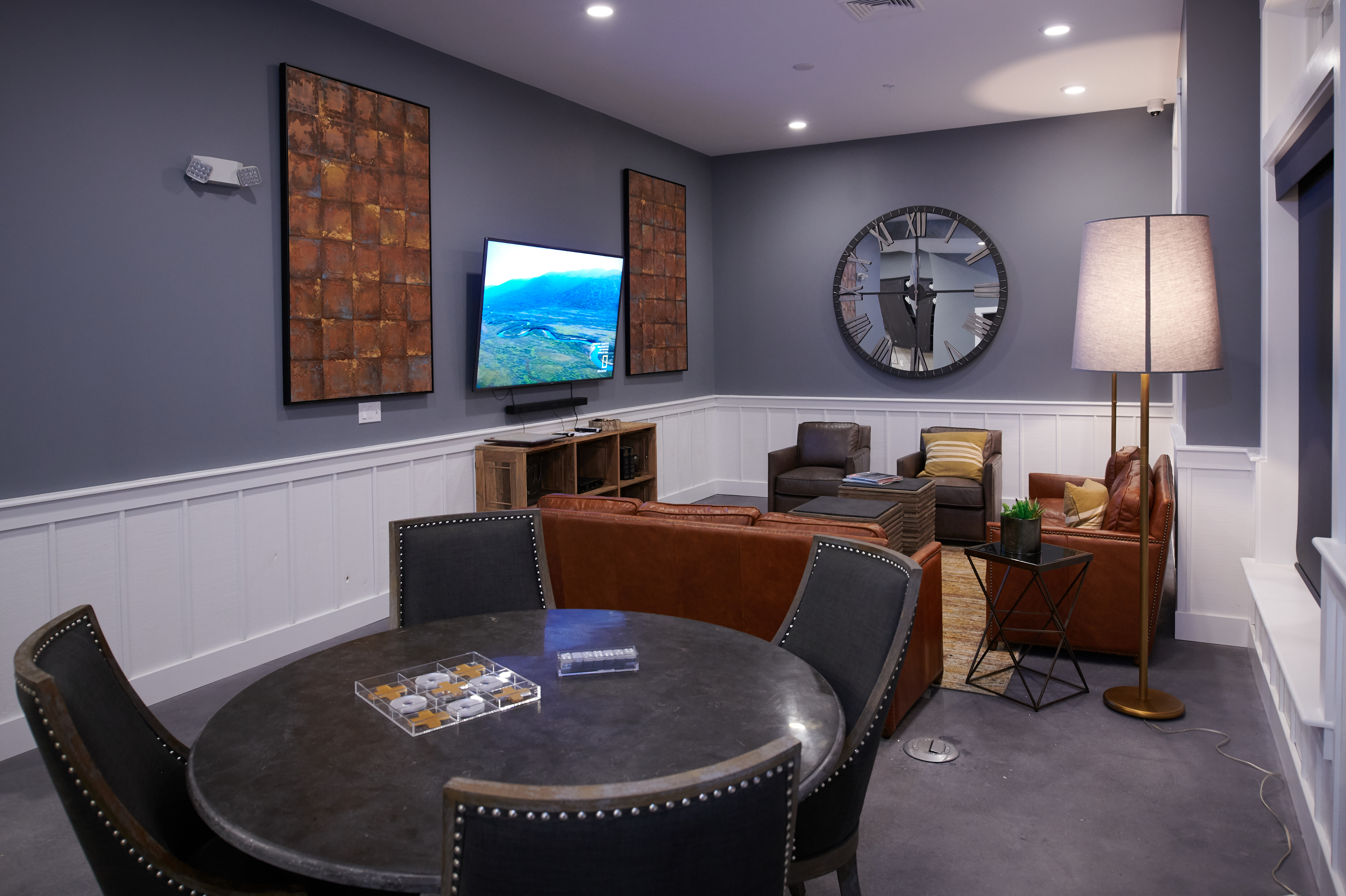 Clubroom at Verde with two couches, two chairs, and round table, and a large television on the wall.