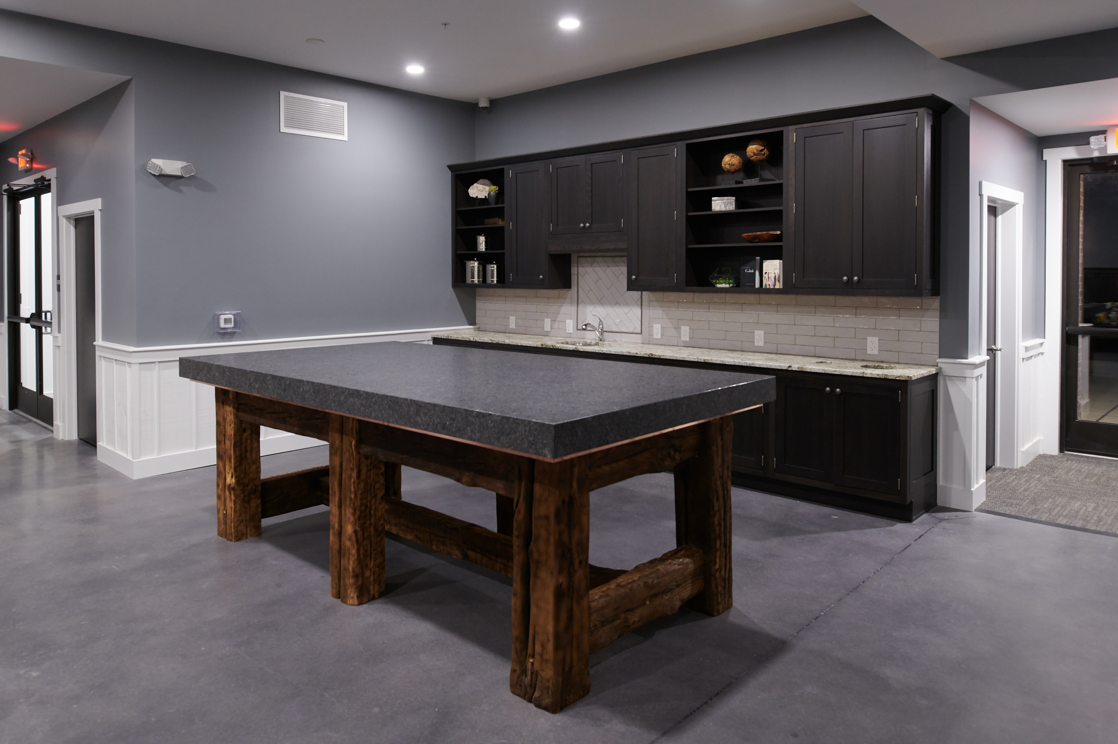 Dining area at the Verde clubhouse with a large island, dark brown cabinets, and subway tile backsplash