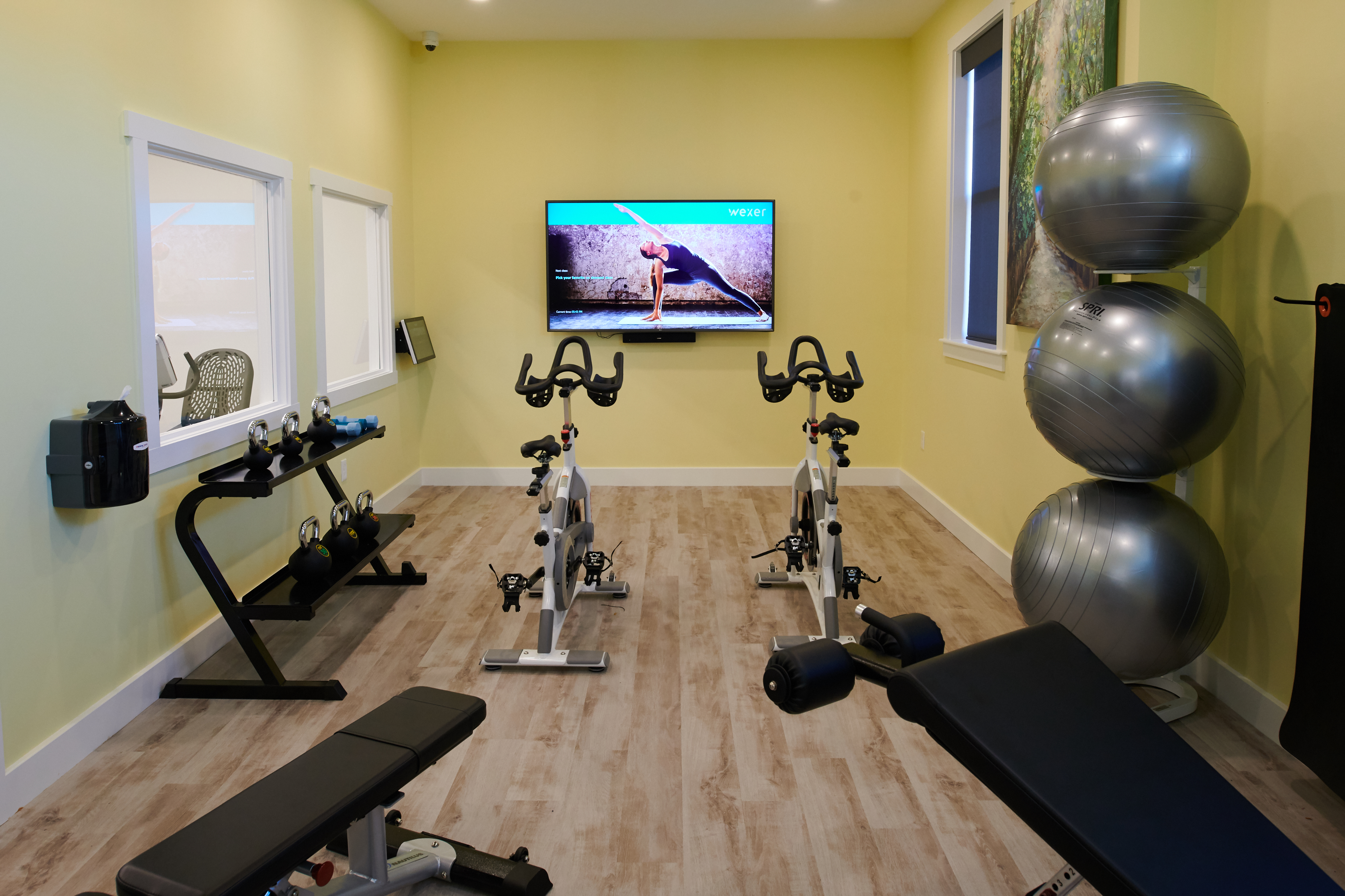 Workout classroom at Verde with kettlebells, benches, and two spin bikes.